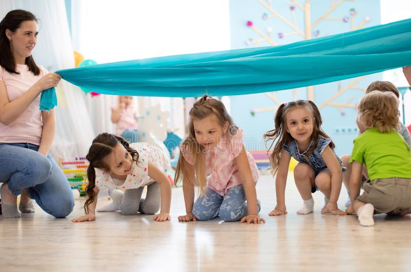 Children crawling under stretched fabric. Active games in preschool or kinfergarten royalty free stock photography
