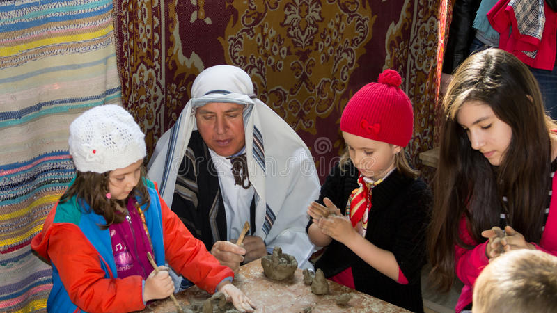 Children creating objects from clay. In Biblical Village. The Biblical Village is the first project in Europe organized in Bucharest at Titan Park and stock photo