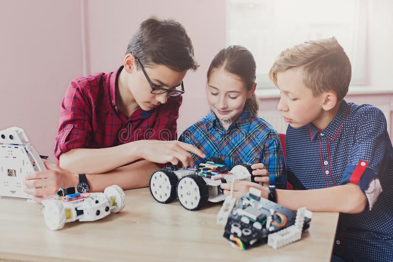 Stem education. Kids creating robots at school stock photo