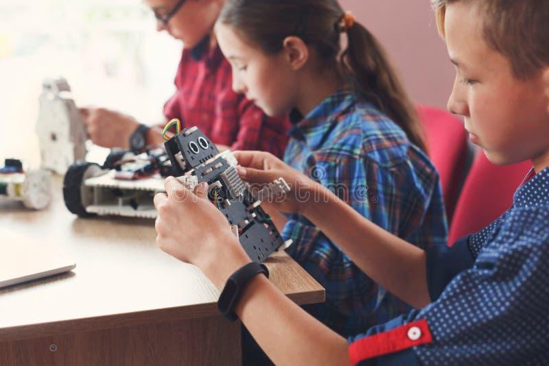 Stem education. Kids creating robots at school stock photos