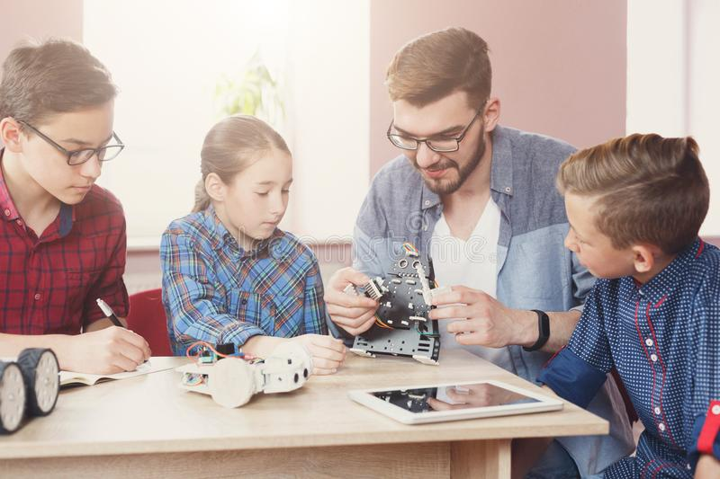 Stem education. Kids creating robots with teacher royalty free stock images