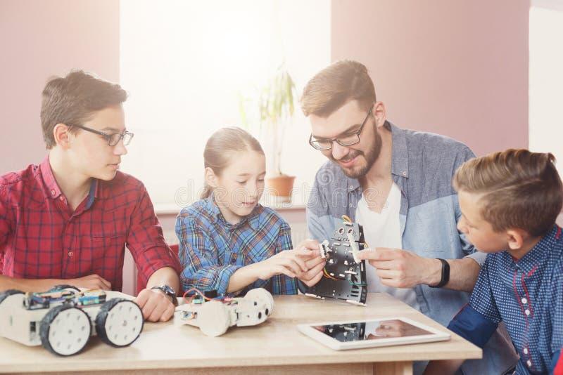 Stem education. Kids creating robots with teacher stock photo