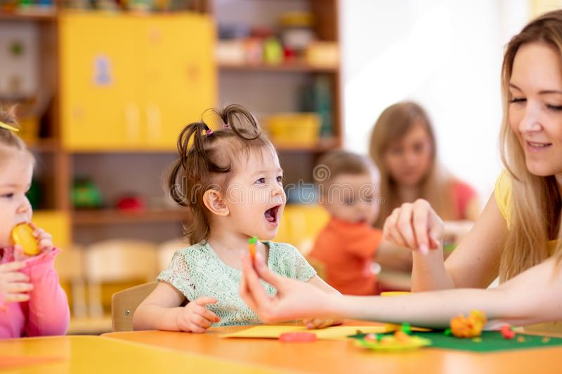 Children creativity. Kids sculpting from clay. Cute little girl mould from plasticine on table in kindergarten royalty free stock photo