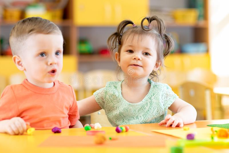 Children in creche. Kids sculpting from clay. Cute little boy and girl mould from plasticine on table in nursery royalty free stock image