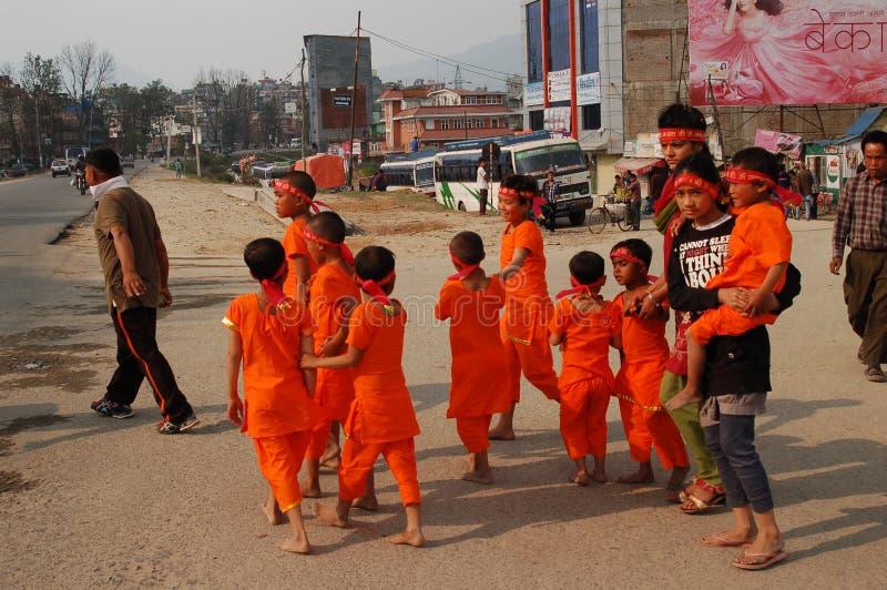 Children cross a street in Kathmandu, Nepal. A group of children in orange clothing cross a street in Kathmandu, Nepal royalty free stock image