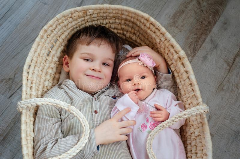 Children, cute little boy 5 years old, with him newborn sister lies in a wicker cradle stock image