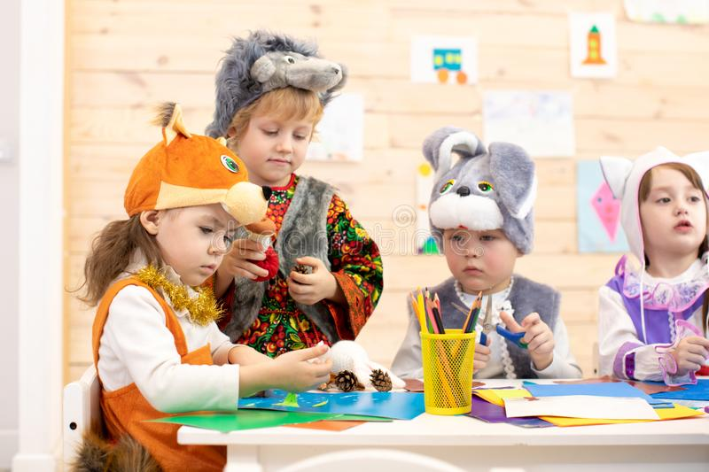Children cutting out scissors paper in preschool or daycare stock image
