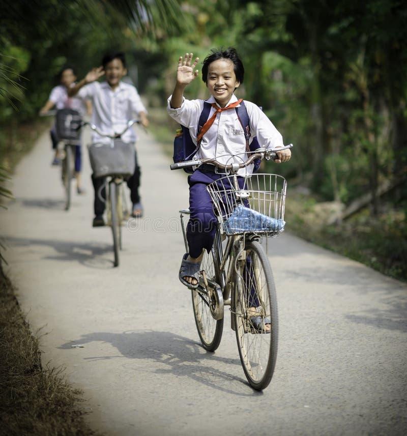 School children in vietnam. Children cycling home from school in the mekong delta in vietnam royalty free stock photography