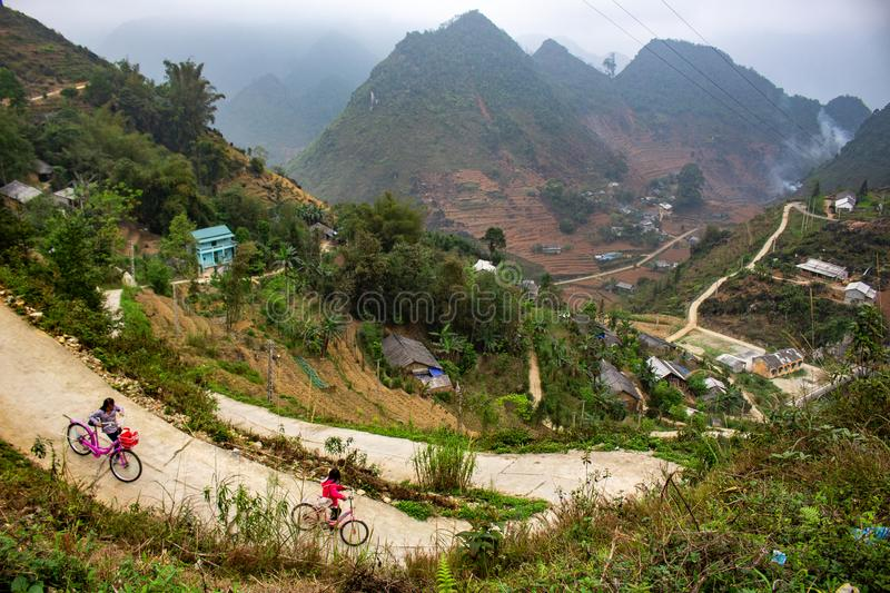Children cycling in the mountains. Ha Giang, Vietnam - March 18, 2018: Children cycling in a village surrounded by mountains and fog in the northernmost province royalty free stock image