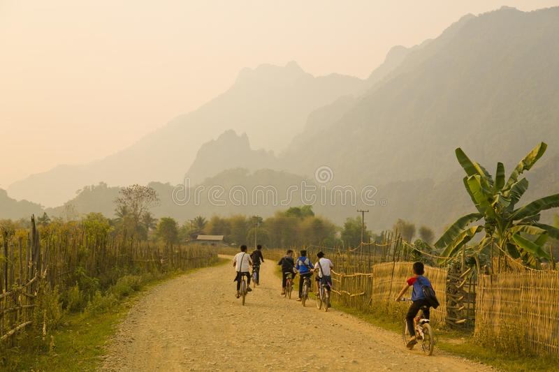 Children cycling, Sunset at limestone mountains of Vang Vieng, Laos royalty free stock photography