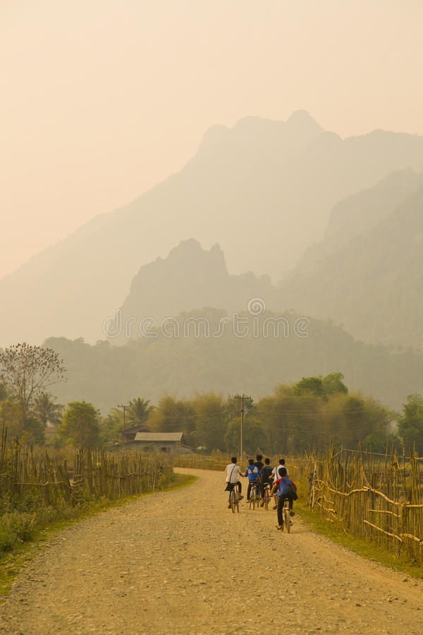 Children cycling, Sunset at limestone mountains of Vang Vieng, Laos stock photo