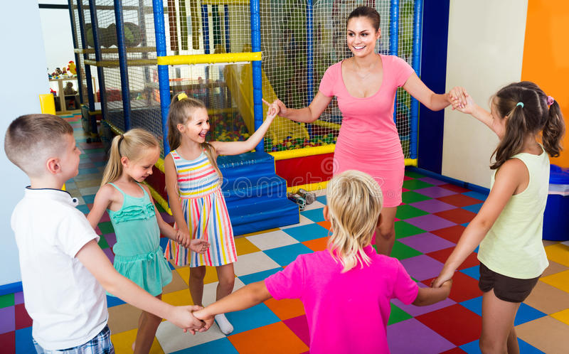 Children dancing with teacher to music in class at school. Happy children dancing with teacher to music in class at school royalty free stock photo