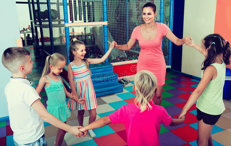 Children dancing with teacher to music in class at school. Happy children dancing with teacher to music in class at school royalty free stock photos