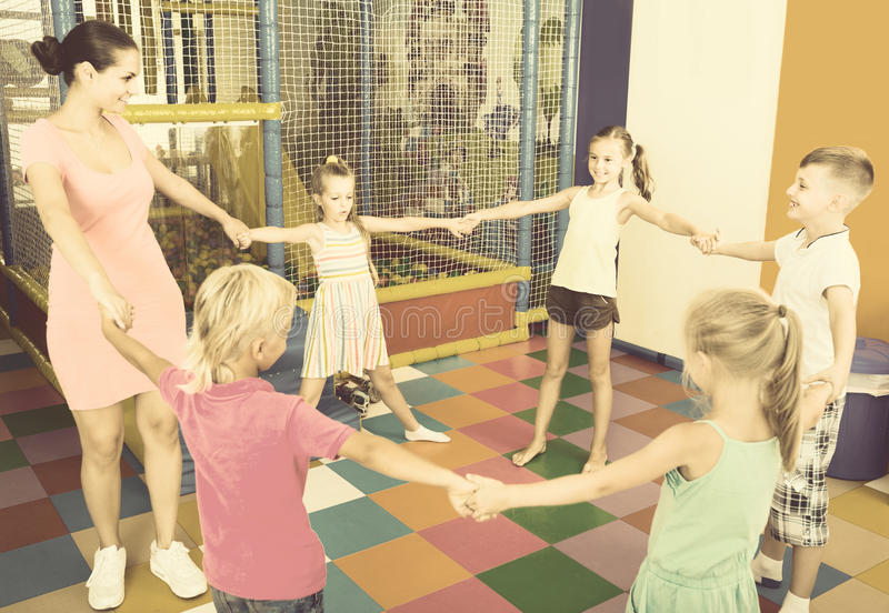 Children dancing with teacher to music in class at school. Happy spanish children dancing with teacher to music in class at school stock photography