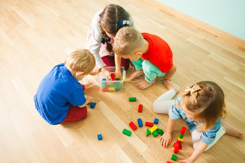 Children at day care centre putting toys into box stock photos