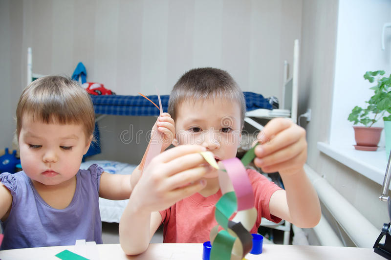 Download Children Development - Kids Making Paper Colored Garland, Brother And Sister Crafting Stock Photo - Image: 83720094