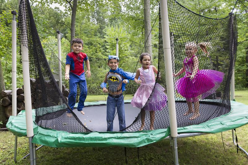 Children disguised as super-heroes or princesses jumping on trampoline royalty free stock photos