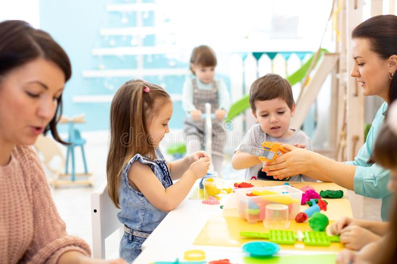 Children dough play in daycare centre. Kids mold from plasticine in kindergarten. Little students knead modeling clay with hands stock photo