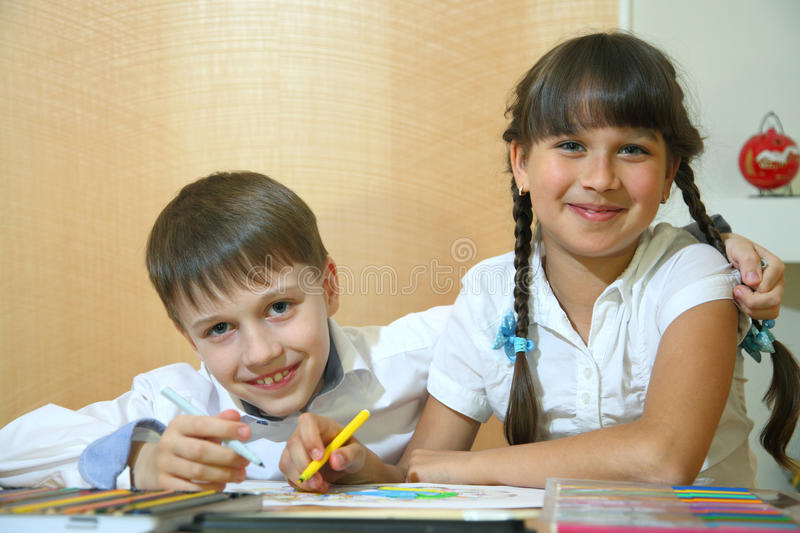Children draw on paper. Creativity and education concept. The child paints with colored pencils on a white sheet of paper table royalty free stock photos