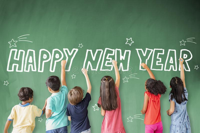 Children drawing happy new year on the chalkboard. School children drawing happy new year on the chalkboard stock photography