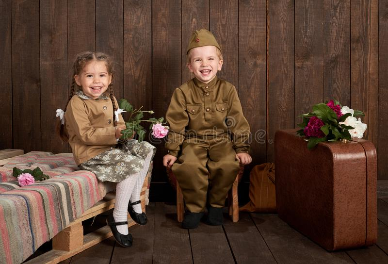 Children are dressed in retro military uniforms sending a soldier to the army, dark wood background, retro style royalty free stock images