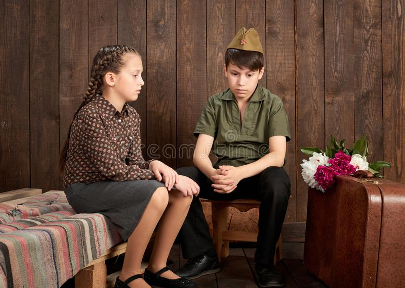 Children are dressed in retro military uniforms sending a soldier to the army, dark wood background, retro style stock photo