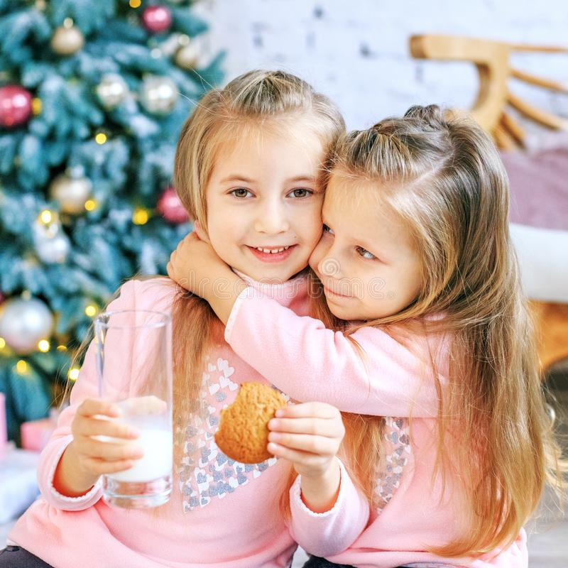 Children drink milk and eat oatmeal cookies. Girls hugging. Brea stock photos
