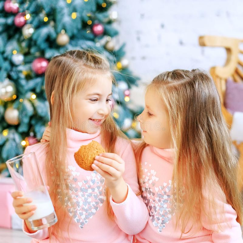 Children drink milk and eat oatmeal cookies. Girls talk. Breakfa. St. Concept New Year, Merry Christmas, holiday, vacation, winter, childhood stock images