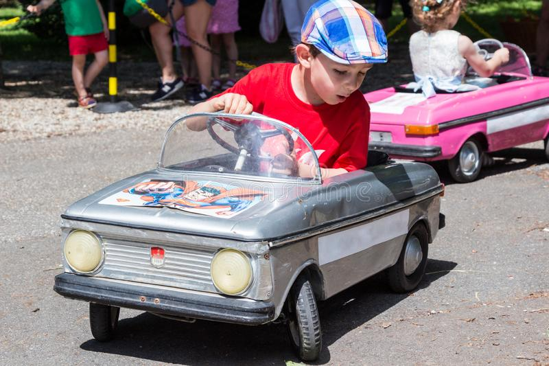 Children driving retro metal pedal cars royalty free stock photo