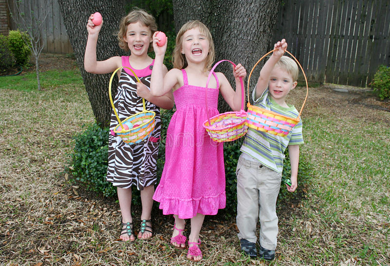 Children Easter Egg Hunt. Three little kids hold up their baskets and show the Easter eggs they found on an Easter egg hunt royalty free stock images
