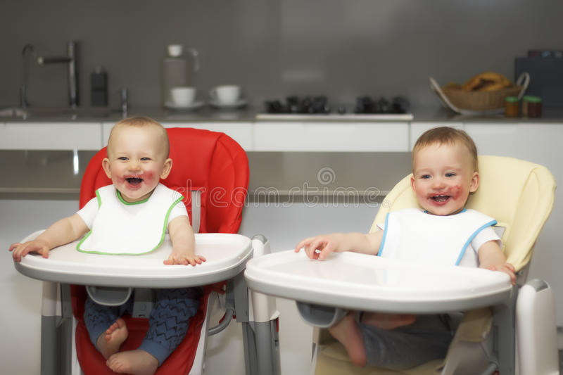 Children eat blueberries in a high baby chair. The boys have a dirty face stock photos