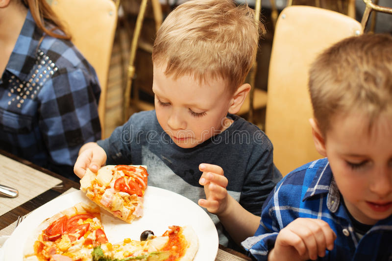 Children eat Italian pizza in the cafe royalty free stock images
