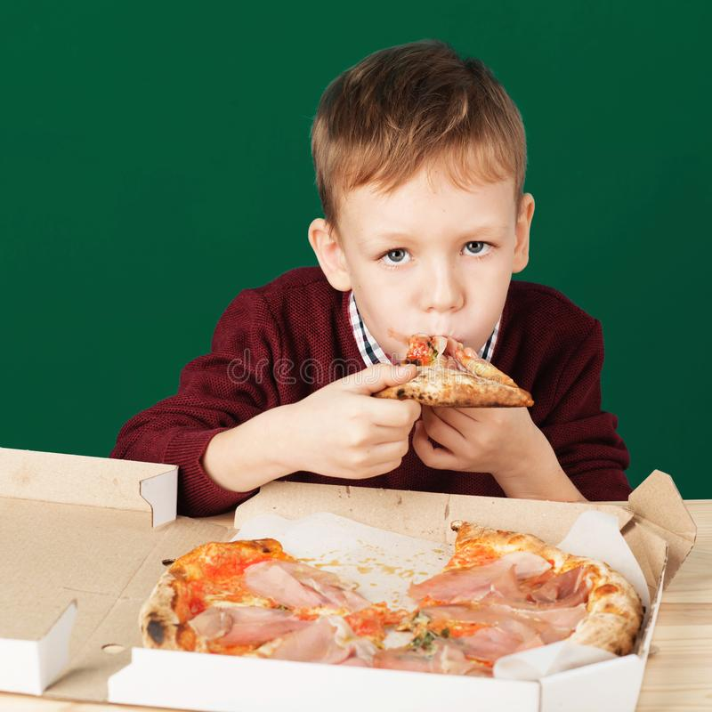 Children eat Italian pizza in the cafe. School boy eating pizza stock photo