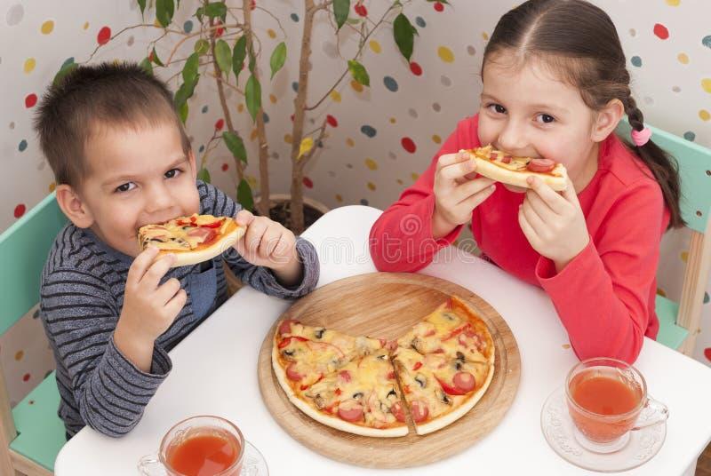 Children eat pizza stock images