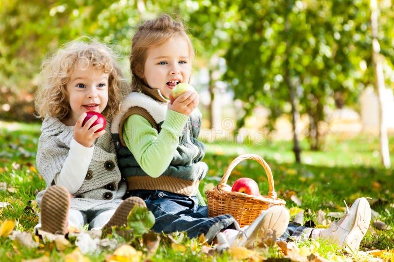 Children eating apples stock photography