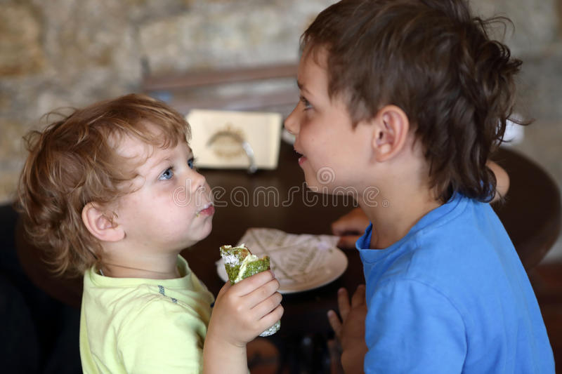 Children eating eclair royalty free stock images