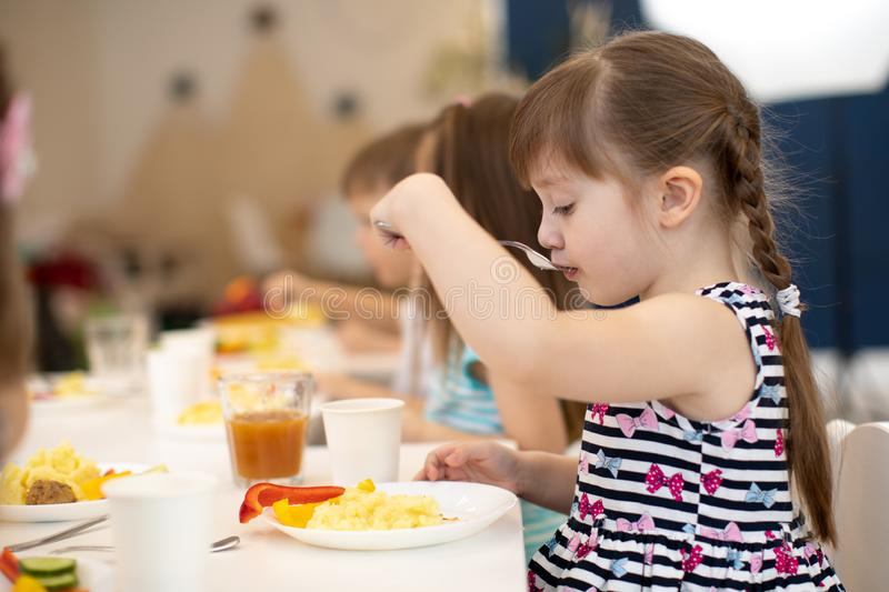 Children eating food in daycare centre or kindergarten. Children eating healthy food in daycare centre or kindergarten stock images