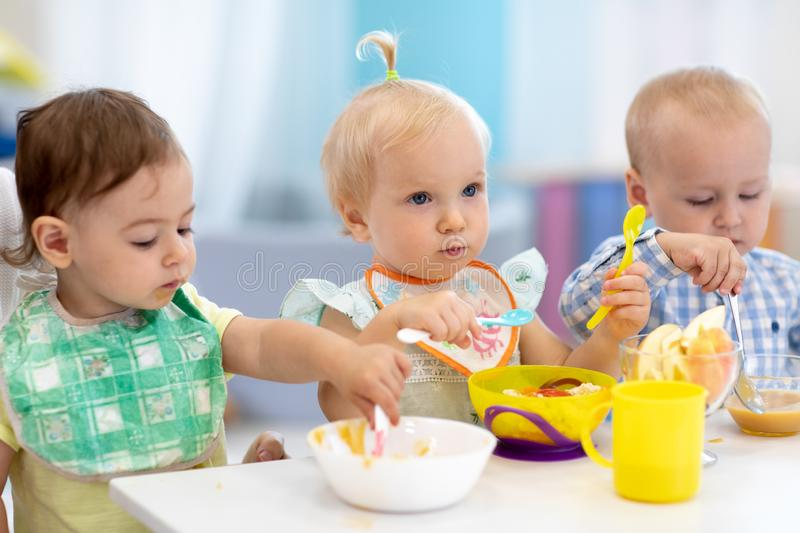 Children are eating food in the nursery. Lunch in daycare. Children are eating healthy food in the nursery. Lunch in daycare royalty free stock images