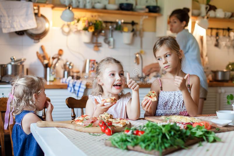 Children are eating italian homemade pizza. Cute kids are having fun while enjoying delicious food in cozy home kitchen. stock images
