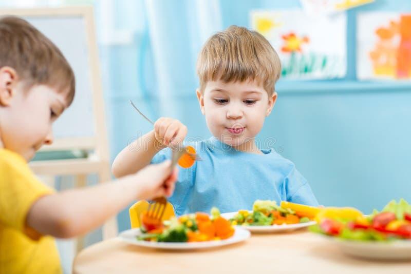 Children eating in kindergarten. Children eating vegetables in kindergarten or at home