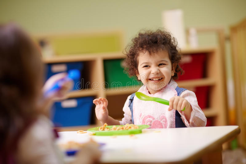 Children eating lunch in kindergarten royalty free stock photography