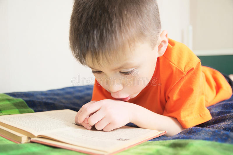 Children education, boy reading book lying on bed, child portrait with book, interesting storybook stock images