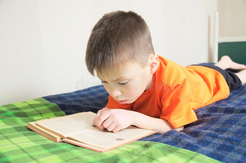 Children education, boy reading book lying on bed, child reading book with interest, educational interesting storybook stock photography