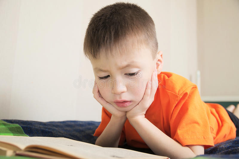 Children education, child reading book lying on bed, boy portrait with book, interesting storybook stock photo