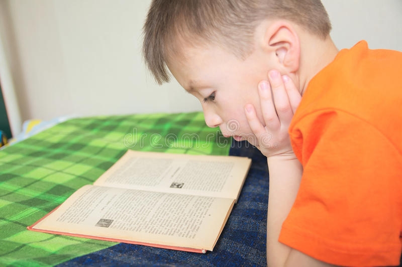 Children education, kid reading book lying on bed, serious child read with book, education, interesting fairy tale royalty free stock photos