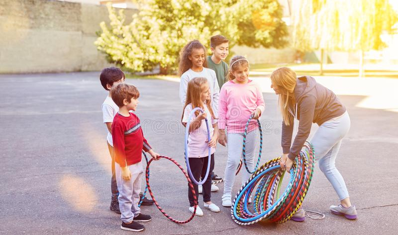 Children do sports on school playground with tires. Children in elementary school together do sports on school playground with tires and sports teacher royalty free stock image