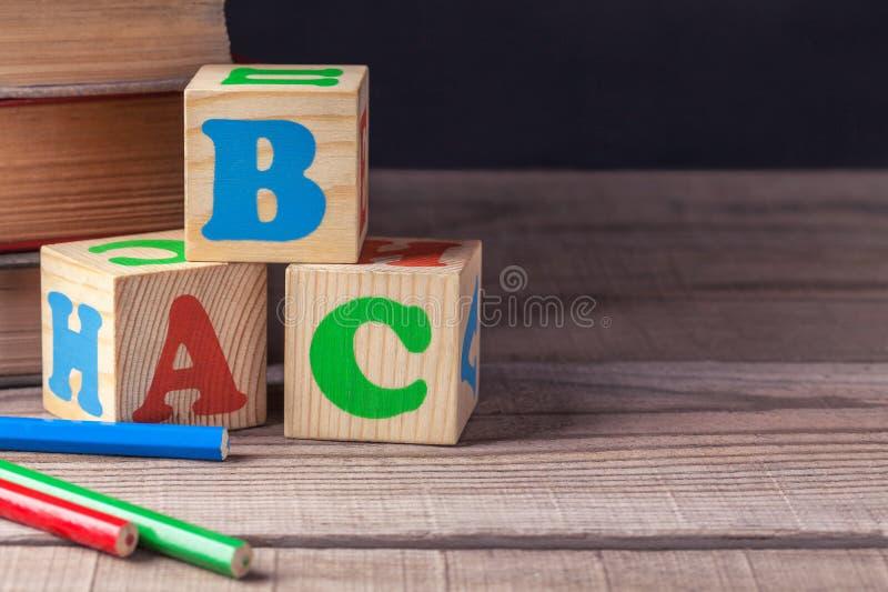 Children& en bois x27 ; blocs de s avec des lettres et plan rapproché coloré de crayons, mensonge sur une table en bois photographie stock