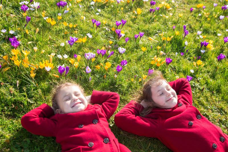 Children enjoy spring, sun and flowers stock photography