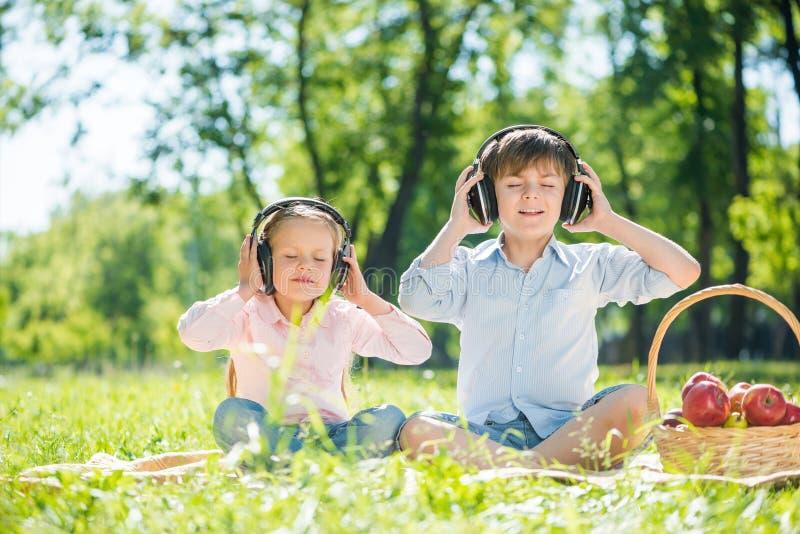 Children enjoying music. Little cute boy and girl in summer park stock photo