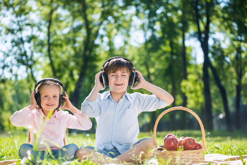 Children enjoying music. Little cute boy and girl in summer park royalty free stock photography